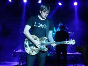 Tom Delonge wearing an Angels and Airwaves shirt.