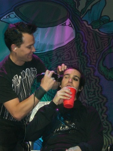 Mark Hoppus shaving Pete Wentz's head.